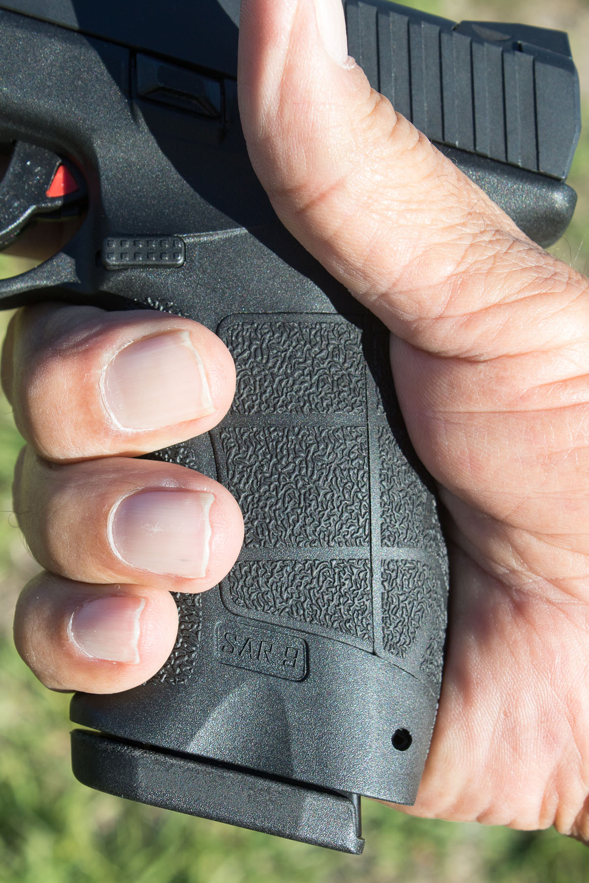 "Grip configuration of SAR9 reminds many of H&K, and was liked by all who participated in test. Note thumb safety, here ""on safe."""