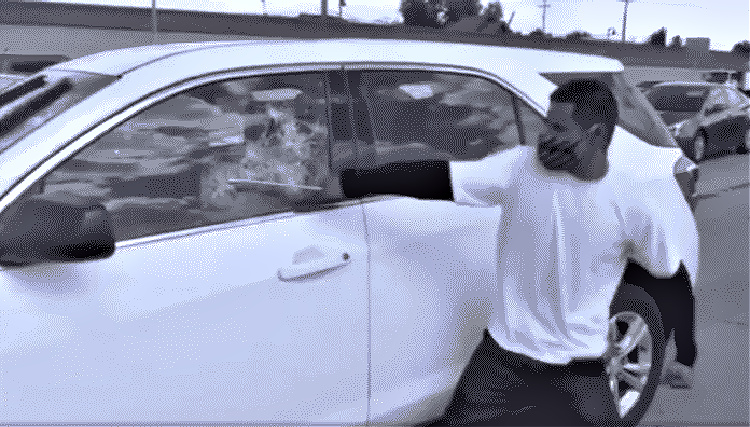how to survive a riot in your vehicle. Image of man smashing in car window.